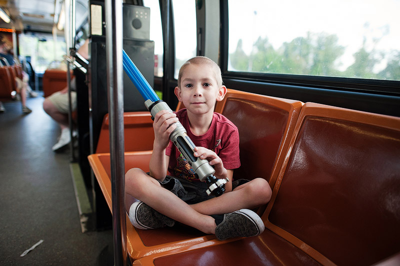 Boy holding custom lightsaber on Disney bus.