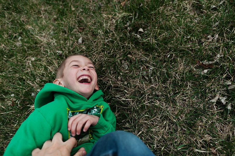 Father tickling his son in the grass.