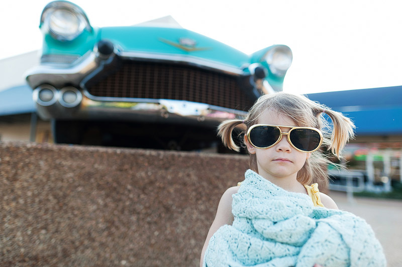 Toddler with Elvis glasses on in front of a vintage car at Graceland.