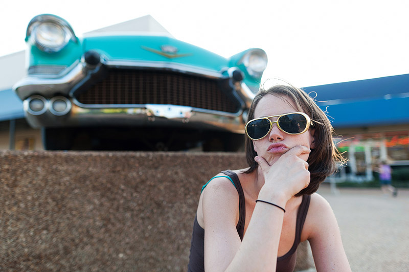 Woman with Elvis glasses on in front of a vintage car at Graceland.