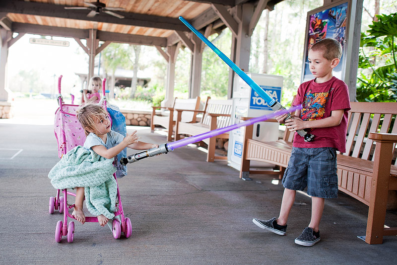 Kids lightsaber fighting at Disney World.