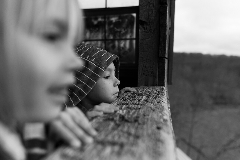 Kids looking out the top of a huge treehouse.