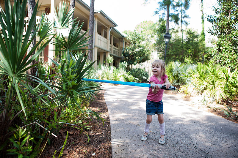 Girl lightsaber fighting trees.