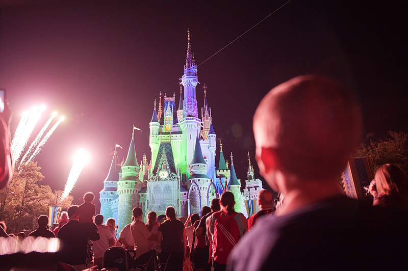 Boy watching fireworks over Cinderella's Castle.