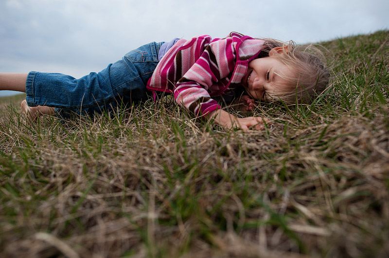 Girl rolling down the hill at Eckert's Farm.