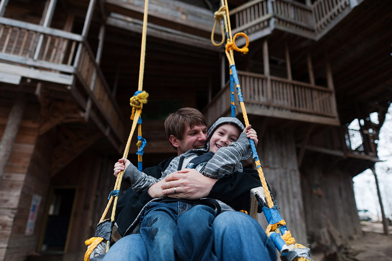 Dad and son laughing while swinging in the biggest swing ever.