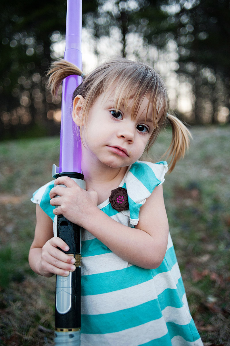 Toddler girl with band-aid and lightsaber.