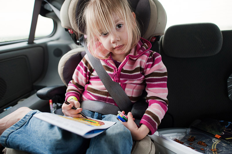 Girl in carseat coloring.