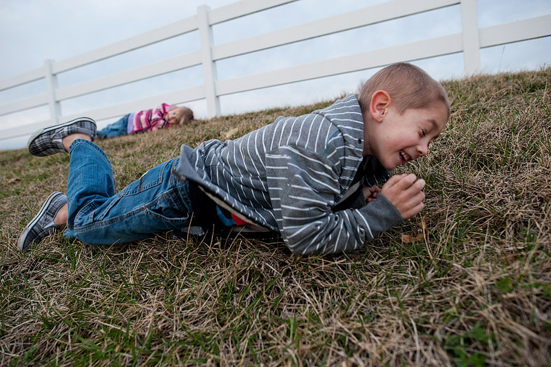 Boy rolling down the hill at Eckert's Farm.