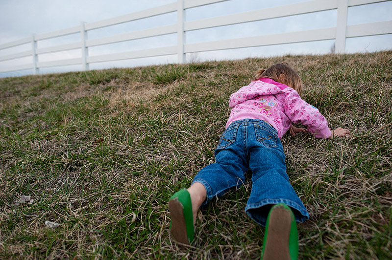 Toddler trying to roll down the hill.