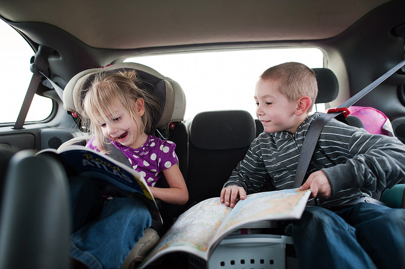 Boy and girl looking at road atlases.
