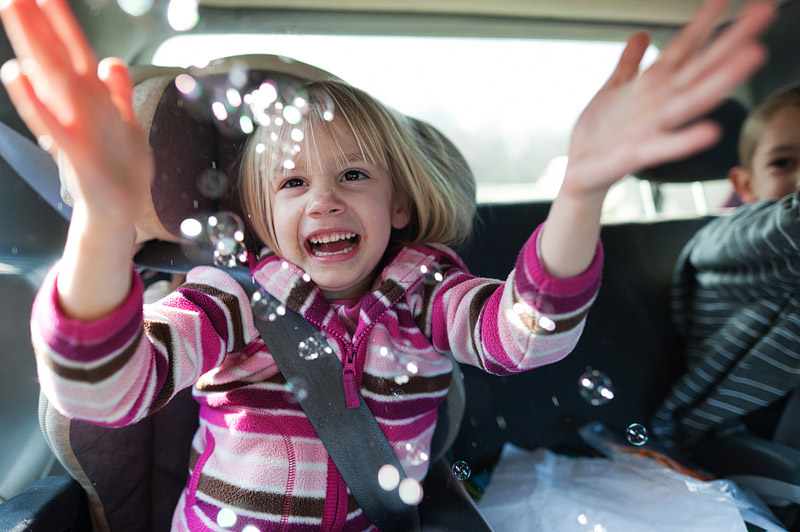 Girl popping bubbles in the car.