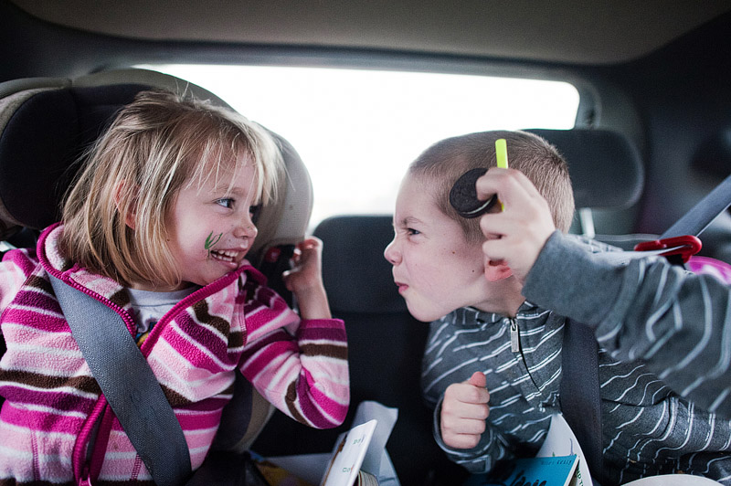 Kids making faces in the car while on a road trip.