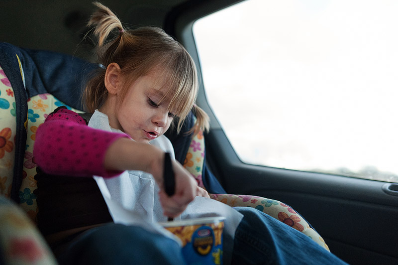 Little girl eating Kraft easy mac in the car during a road trip.