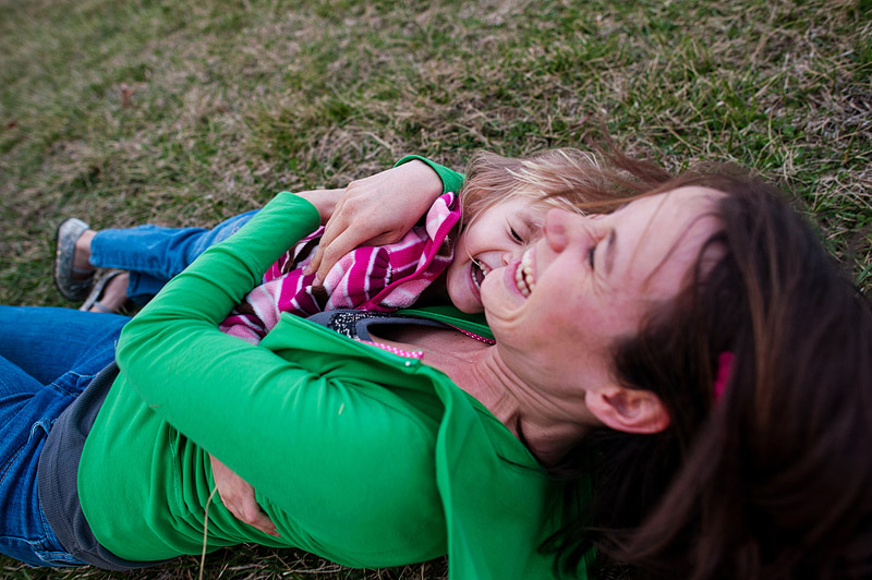 Mom and daughter snuggle in the grass together.
