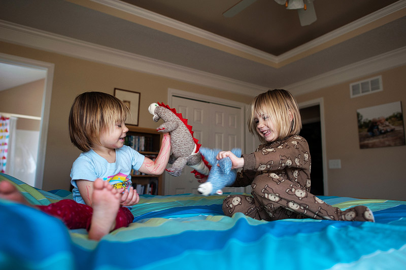 Sisters playing with hand made sock animals.