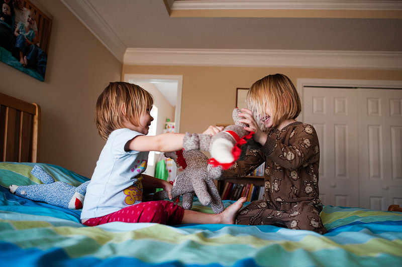 Sisters playing with sock animals.