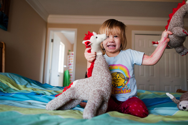 Toddler fighting with sock animals.