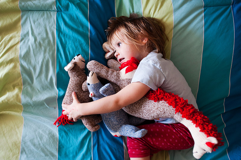 Toddler laying with sock animals.