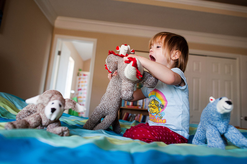 Toddler playinig with sock animals in bed.