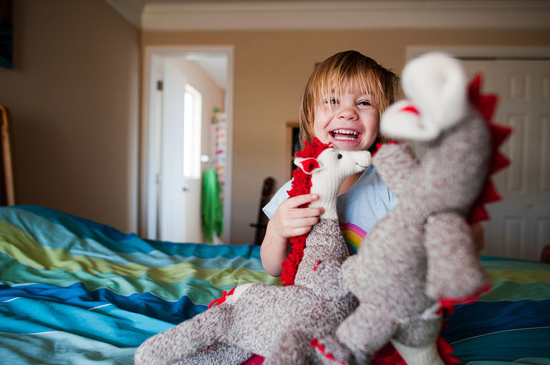 Toddler smiling with sock animals.