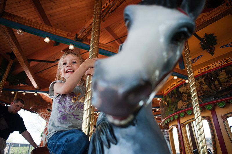Girl rides merry go round horse carousel smiling