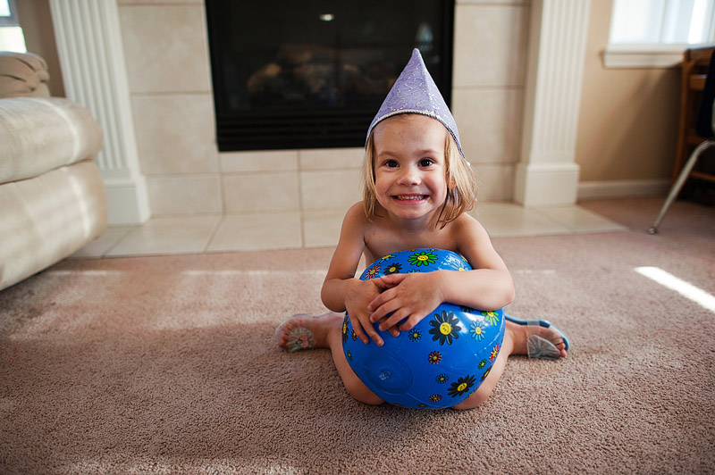 Toddler in a princess hat with a beach ball.