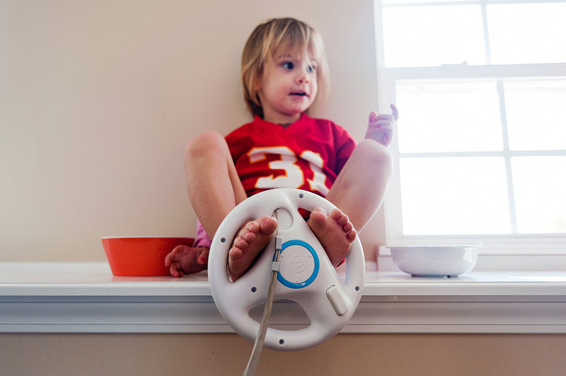 Sitting on ledge toddler and wii steering wheel.