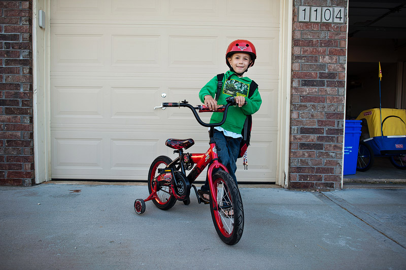 Boy getting ready to ride his bike to school.