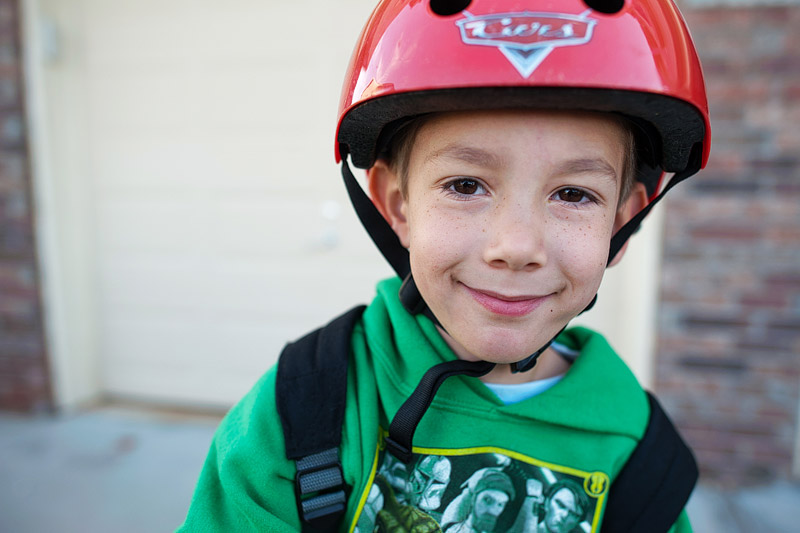 Boy with a cars bike helmet on.