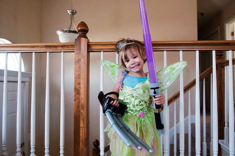 Girl dressed as Tinker Bell with Lightsaber and Wolverine claw.