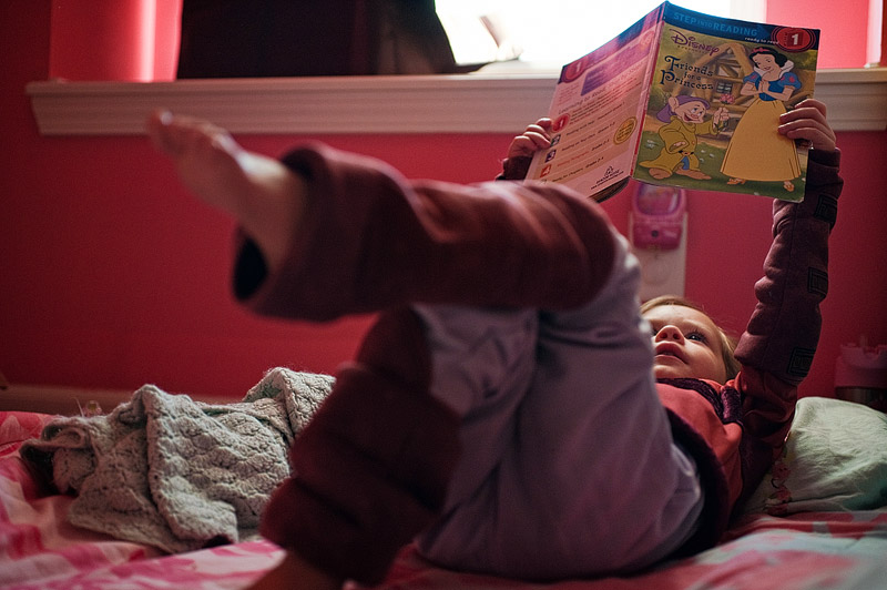 Toddler dressed as Ahsoka from Star Wars Clone Wars reading a book.