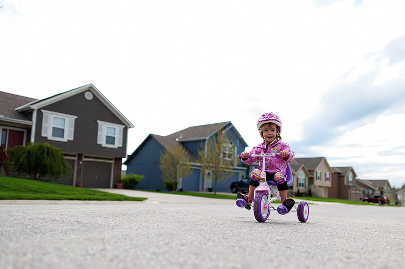 Toddler riding her tricycle.