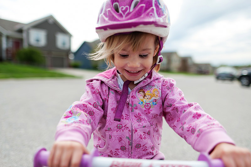 Toddler smiling on her tricycle.
