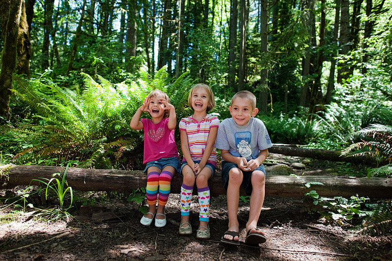 Kids sitting on a log in the Oregon forest.