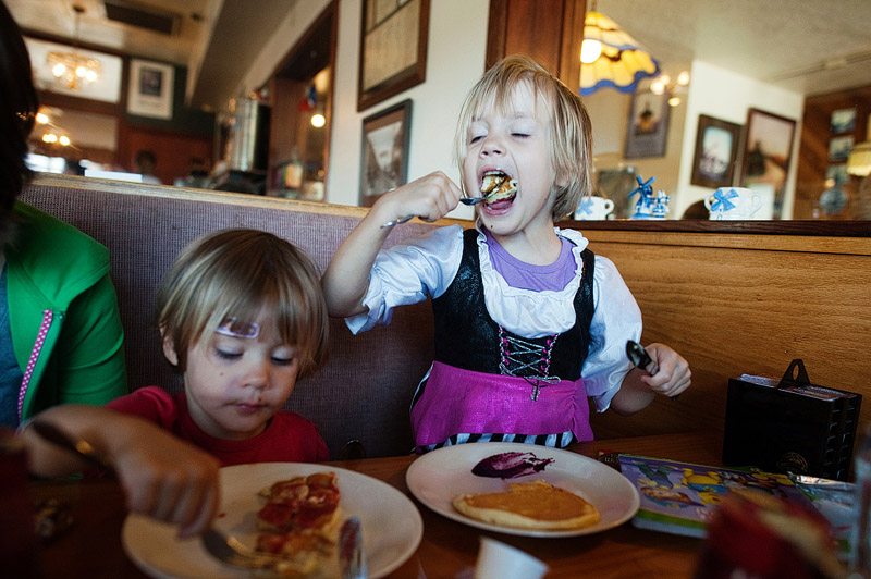 Girl eating pancakes with blueberry syrup in Oregon.