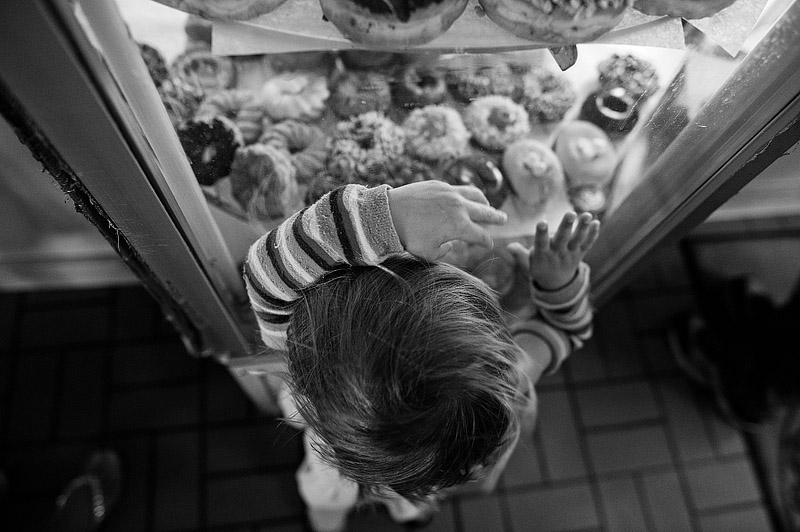 Toddler checking out donut selection at voodoo donuts.