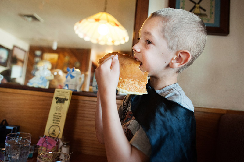 Boy eating pancakes for breakfast.
