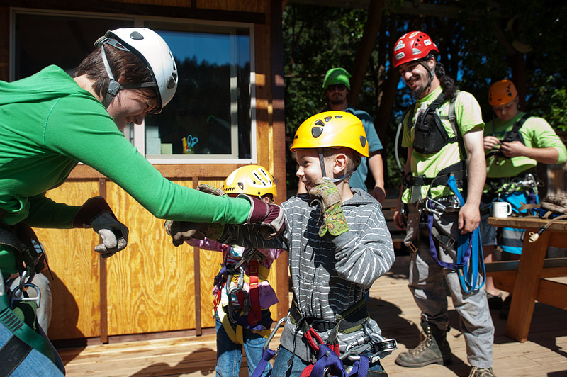 Mom and boy boxing in zip line gear.