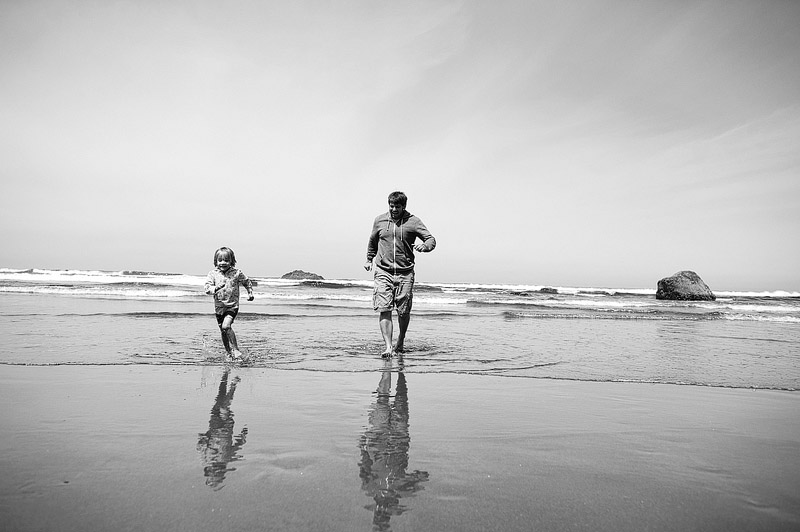 Father and daughter running in the ocean at Hug Point, Oregon.