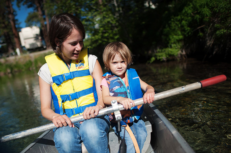 Mom and toddler rowing a canoe.