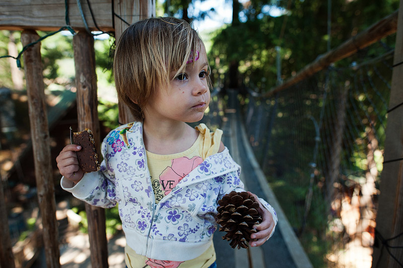 Toddler holding pinecone and a fiber bar.