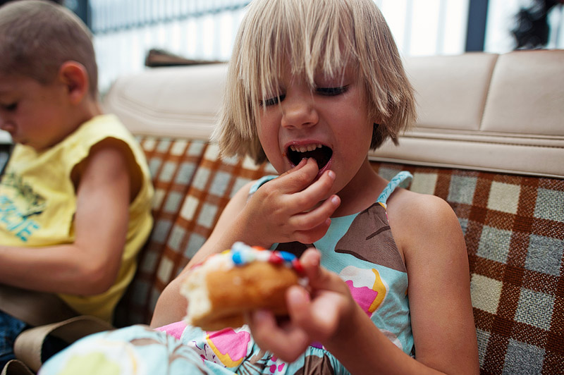 Girl eating a voodoo m&m donut.
