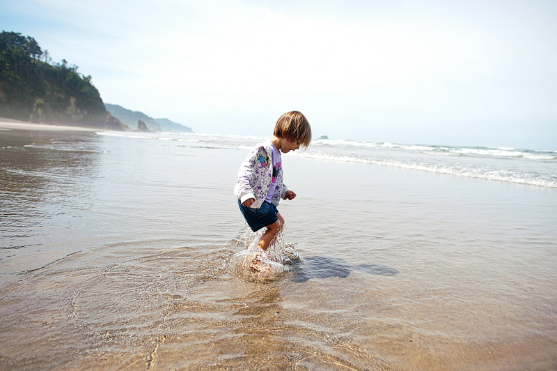 Toddler jumping in the ocean.
