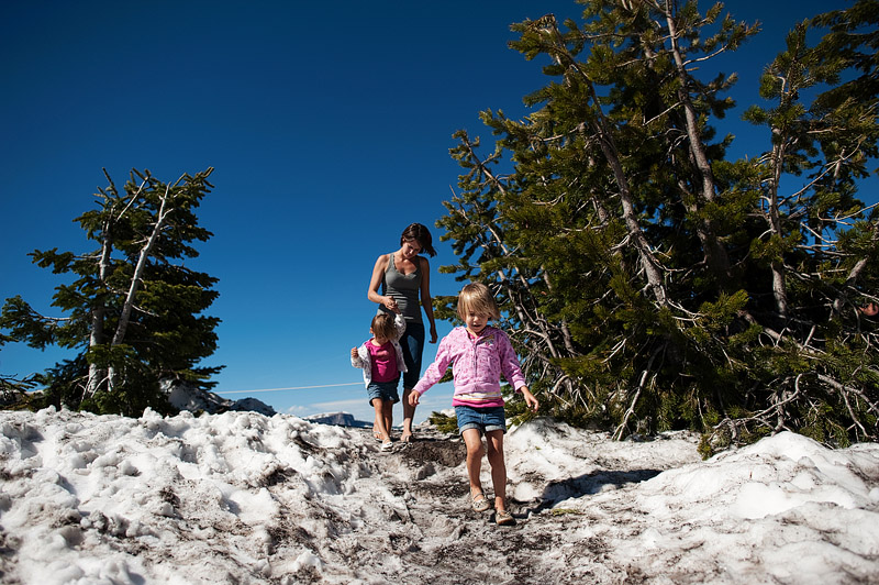 Kids and mom walking down snowy walk at Crater Lake.