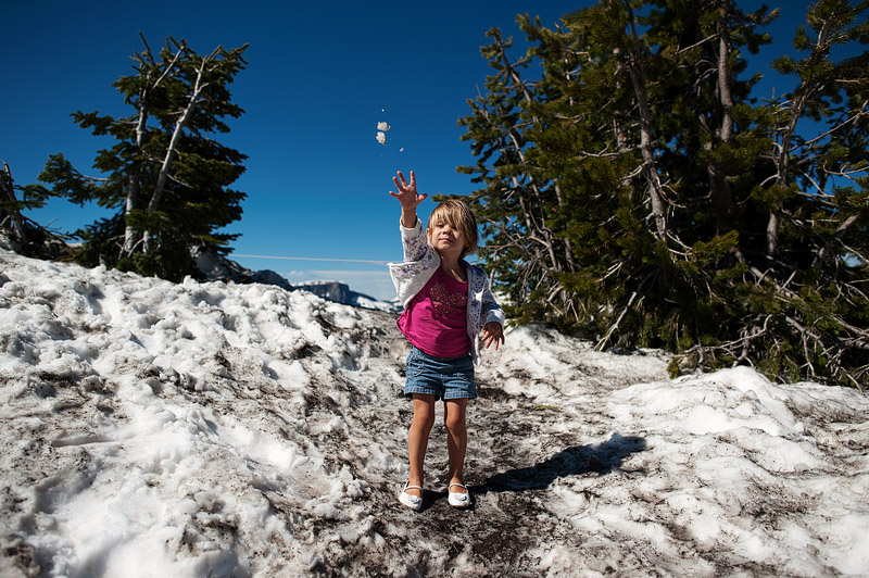 Girl throwing snowball in June at Crater Lake.