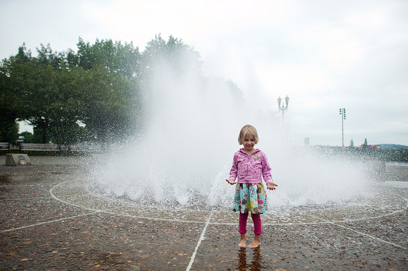 Girl playing in downtown portland fountain.