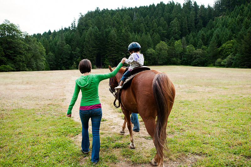 Toddler riding a horse.