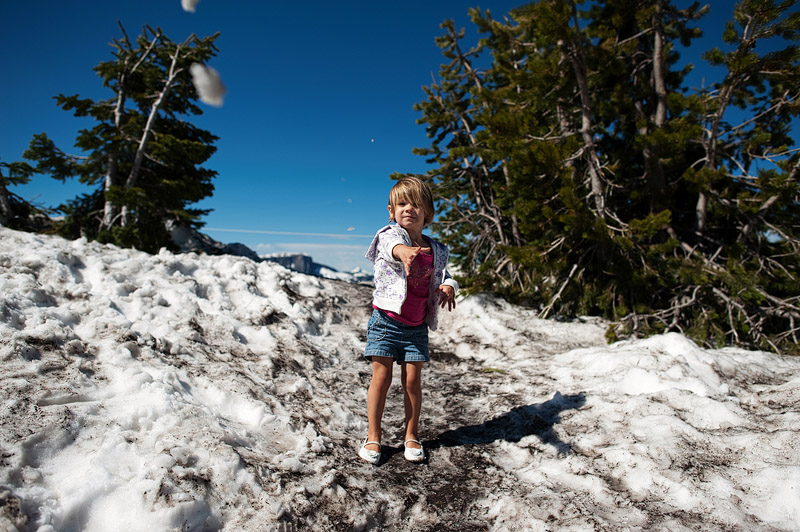 Toddler tossing snow.