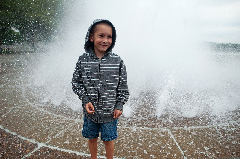 Boy getting wet in the fountain.
